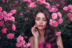 Romantic beauty portrait of woman in pink roses. Fashion style beauty romantic portrait of young pretty beautiful woman with long curly hair posing between pink Stock Photo