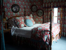 Romantic Bedroom. A four poster bed, lots of pillows, fabric, draperies, wall paper and antiques make up this beautiful bedroom Stock Images