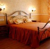 Romantic bedroom. Sunny romantic bedroom designed in orange pastel colours Stock Images