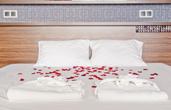 Romantic bedroom in a spa hotel - rose petals and dressing gowns. Lying on a bed stock photography