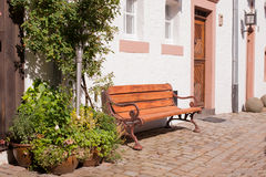 Romantic bench in the sun. Bench in front of an old house and flower pots Stock Photos