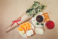 Romantic Birthday Breakfast.Cup of Coffee,Glass og red Beverage,Cut Orange,Biscuit with Cottage Cheese.Wish Card with Flowers. Royalty Free Stock Image