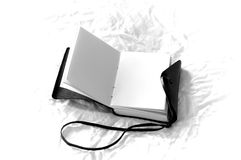 Romantic black and white blank journal. An old fashioned leather bound blank journal  open to show the blank pages in black and white, shot on white fabric Stock Image