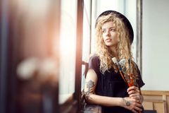 Romantic Blonde Tattoed Artist with Brush. Blonde tattoed curly artist in fancy black hat hold brush near the sunny window royalty free stock photo