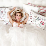 Romantic blonde woman posing in bed Stock Photography