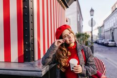 Romantic blue-eyed woman in beret dreamy posing with cup of coffee. Outdoor portrait of graceful curly lady tasting