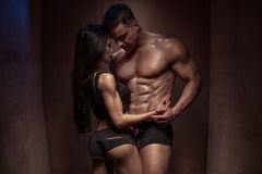 Romantic Bodybuilding Couple Against Wooden Wall. Portrait of a Romantic Young Bodybuilding Couple with Bodies Posing so Closed Against a Brown Wooden Wall royalty free stock image