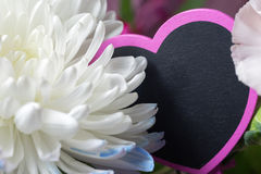 Romantic bouquet of flowers closeup with pink heart chalkboard s. Ign tag, space for text Stock Photo