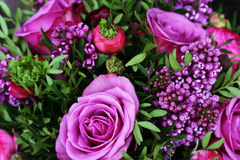 Romantic bouquet with purple roses. Bouquet of purple flowers (lilac and roses) with green leaves stock photo