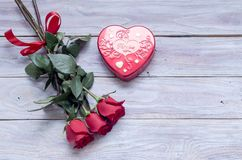 Romantic bouquet of red roses and box with candies stock photos