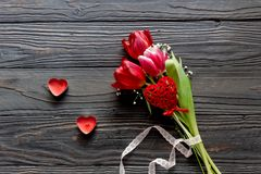 Romantic bouquet of tulips and red candles. Composition for Valentine`s Day. Romantic bouquet of tulips and red candles on a wooden table close-up Stock Images