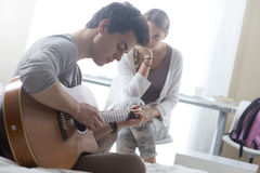 Romantic boy playing guitar for her girlfriend. Young handsome men playing guitar for his girlfriend stock photo