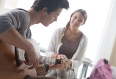 Romantic boy playing guitar for her girlfriend Stock Photo