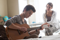 Romantic boy playing guitar for her girlfriend Stock Photos