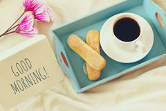 Romantic breakfast in the bed: cookies, hot coffee, flowers Stock Photo
