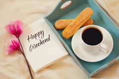 Romantic breakfast in the bed. Cookies, hot coffee, flowers and note with the text: HAPPY WEEKEND Royalty Free Stock Images