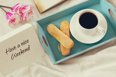 Romantic breakfast in the bed. Cookies, hot coffee, flowers and note with the text: HAVE A NICE WEEKEND Royalty Free Stock Photography