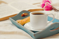 Romantic breakfast in the bed: cookies, hot coffee, flowers and Royalty Free Stock Photography