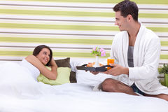 Romantic breakfast in bed. Man serving women a romantic breakfast in bed Stock Photo