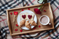 Romantic breakfast in bed for Valentines Day. Toasts with jam, croissants, hot chocolate, red rose flower and petals Stock Photos