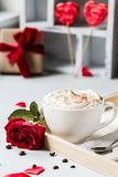 Breakfast coffee love heart red rose setting with white mug and gift box in Valentine`s day setting. Romantic breakfast coffee for Valentines day surprise for Royalty Free Stock Images