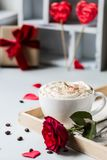 Breakfast coffee love heart red rose setting with white mug and gift box in Valentine`s day setting. Romantic breakfast coffee for Valentines day surprise for Royalty Free Stock Image