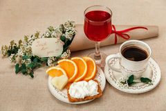 Romantic Breakfast.Cup of Coffee,Cut Orange,Biscuit with Cottage Cheese.Glass of Red Drink.Wish Card with Flowers. Congratulation Poscard Royalty Free Stock Images