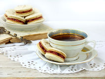 Romantic breakfast with cup of espresso coffee and French macaroons dessert. On light wooden background Stock Photo