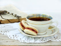Romantic breakfast with cup of espresso coffee and French macaroons dessert. On light wooden background Stock Photos