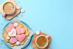 Romantic breakfast with heart shaped cookies and cups of coffee on color background, flat lay. Space for text stock photos