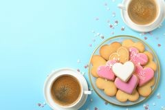 Romantic breakfast with heart shaped cookies and cups of coffee on color background. Flat lay. Space for text royalty free stock images