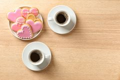 Romantic breakfast with heart shaped cookies and cups of coffee on wooden table, top view. Space for text stock image