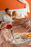 Romantic breakfast hotel room service young couple. Watching bed stock image