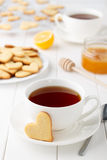 Romantic breakfast for lovers on Valentines day: two cups of tea and heart shaped cookies on white wooden table. Stock Photography