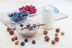 Romantic breakfast of oatmeal, blueberries, honey, milk and biscuits Royalty Free Stock Images