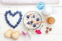 Romantic breakfast of oatmeal, blueberries, honey, milk and biscuits Stock Photography