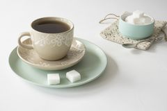 Romantic breakfast scene with cup and saucer, tea, mint green bowl with sugar cubes royalty free stock photos