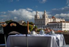 Romantic breakfast on a terace with view on Lisbon, Portugal. Table decked for breakfast with church in the background stock photography