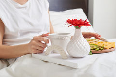 Romantic breakfast on tray decorated with red flower for lover. Cropped of healthy romantic bed breakfast with tea, avocado, cheese on tray decorated with red Royalty Free Stock Photos
