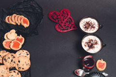 Romantic breakfast. Two Cups of coffee, cappuccino with chocolate cookies and biscuits  near red hearts on black table background. Royalty Free Stock Photography