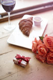 Romantic breakfast for Valentine`s Day celebrate concept. Fresh bakery croissant, red wine, rose flowers on wooden table. Stock Images