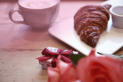 Romantic breakfast for Valentine`s Day celebrate. Present box, rose flowers, fresh croissant coffee on wooden table. Focus at box Royalty Free Stock Image