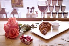 Romantic breakfast for Valentine`s Day celebrate. Present box, rose flowers, fresh croissant, wine on wooden table. Focus on crois Royalty Free Stock Photography