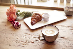 Romantic breakfast, Valentine`s Day celebrating. Present box, rose flowers, fresh croissant, coffee on wooden table. Focus on cup. Royalty Free Stock Image