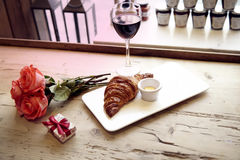 Romantic breakfast, Valentine`s Day celebrating. Present box, rose flowers, fresh croissant, wine on wooden table. Focus on flower Royalty Free Stock Image