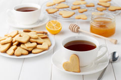 Romantic breakfast on Valentines day with cookies in shape of heart and tea on white wooden table. Royalty Free Stock Photos