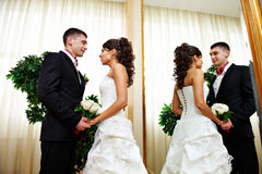Romantic bride and groom near mirror Stock Photos