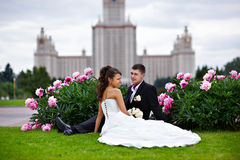 Romantic bride and groom in park of peony flowers Stock Photos