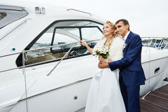 Romantic bride and groom on the pier with yacht. Romantic bride and groom at wedding day on the pier with yacht Stock Image