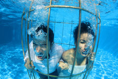 Romantic bride and groom underwater in a bird cage Royalty Free Stock Photography